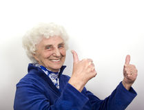 Thumbs Up Granny. A granny with white hair and blue eyes gives an enthusiastic thumbs up stock photo