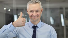 Thumbs Up by Grey Hair Businessman Looking at Camera stock footage