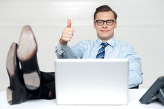 Thumbs up guy relaxing with legs on work desk Stock Photography