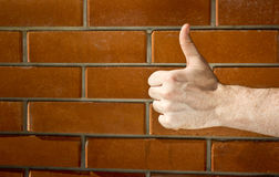 Thumbs up hand. Human hand showing sign of okay/thumbs up on a brick wall background.Image with a copy space stock image