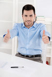 Thumbs up: Happy proud businessman sitting in his office wearing Stock Images