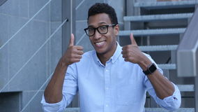 Thumbs Up by Happy Young Black Man Sitting on Stairs stock video footage