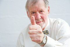 Thumbs up... we have won. An image of a Senior with selective focus giving the thumbs up sign to indicate a positive outcome or a win Stock Photography