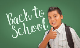 Thumbs Up Hispanic Boy in Front of Back To School Chalk Board. Cute Hispanic Boy With Thumbs Up Wearing A Backpack In Front of Chalk Board with Back To School Royalty Free Stock Photos