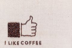 Thumbs up with `I like coffee` made from coffee beans on linen texture, arranged bottom left stock photo