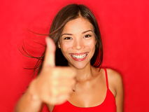 Thumbs up like woman happy. Thumbs up like woman smiling happy with natural beautiful smile on red background. Cheerful and joyful multiracial Asian / Caucasian royalty free stock images