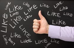 Thumbs Up for Likes. A Social Media concept with a male hand giving a thumbs gesture on a blackboard, where the word like has been written in white chalk Royalty Free Stock Photography