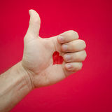 Thumbs up for love. Thombs up for love suggested by a heart on a man's palm over a red background but also suggesting next relationship or moving on Royalty Free Stock Images