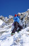 Male backcountry skier hiking to a high alpine summit in Switzerland along a rock and snow ridge. Thumbs up from a male backcountry skier hiking to a high alpine Royalty Free Stock Photos