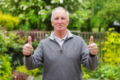 Thumbs up man in garden. Double thumbs up from a smiling happy senior old man in his garden Royalty Free Stock Image