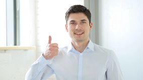 Thumbs Up by Man in Office, Indoor. High quality Stock Photo