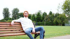 Thumbs Up by Man Sitting on Bench in Park, Red Hairs and Beard. 4k , high quality stock video