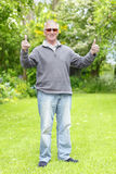 Thumbs up old man in garden Royalty Free Stock Images