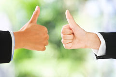Thumbs up over green background Stock Photo