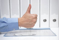 Thumbs up over signed contract and binders Royalty Free Stock Images