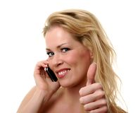 Thumbs up on the phone. Beautiful blonde showing thumbs up when on the phone Royalty Free Stock Photography