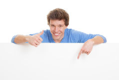 Thumbs up pointing. Happy smiling, young man with thumb up pointing at copy space Stock Photo