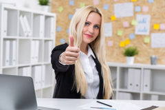 Thumbs up. Pretty businesswoman showing thumbs up in office Stock Photo