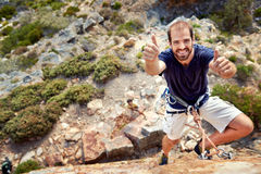 Thumbs up!. A rockclimber with rockclimbing equipment on holding a thumbs up and smiling at  the camera Stock Photography