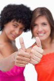 Thumbs up showed by two happy teenage girls. Thumbs up showed by two smiling teenage friends Royalty Free Stock Image