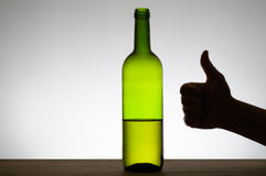 Thumbs up sign and a bottle of wine Stock Image