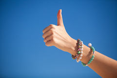 Thumbs up sign on a woman's hand against the Stock Photo