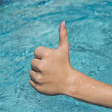 Thumbs up sign of young man, teenager with blue water as backgro. Thumbs up sign of young man with wet hand, teenager with blue water as background Royalty Free Stock Photos