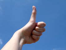 Thumbs up with sky background. Thumbs up (body part) with sky background Royalty Free Stock Photos