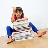 Thumbs up for smart education and reading books for child. A thumbs up for smart education and reading books with a young elementary child with eyeglasses seated Stock Photography
