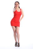 Thumbs up by smiling woman in short red dress Stock Photos