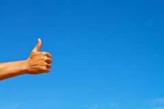 Thumbs up symbol against blue sky Royalty Free Stock Photo