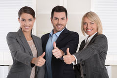 Thumbs up: three successful business people of man and woman in Stock Images