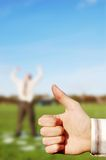 Thumbs up to Business. A businessman with his thumb up with a man cheering in the background royalty free stock images