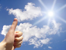 Thumbs Up to Sky. Hand holds the thumbs-up sign to a vibrant blue sky with a light beam shining down through fluffy white clouds Royalty Free Stock Photography