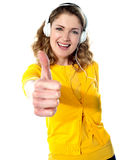 Thumbs-up woman enjoying music Royalty Free Stock Images
