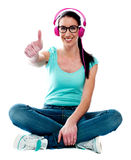 Thumbs-up woman enjoying music Stock Images
