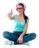 Thumbs-up woman enjoying music Stock Images