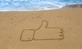 Thumbs up. Written in the sand at the beach Stock Images
