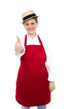 Thumbs up, you cooked the food very well. Lady chef in hat with thumbs up gesture in front of camera Stock Image