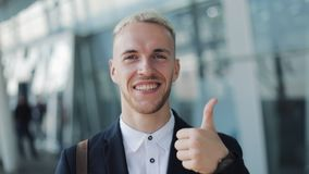 Thumbs Up by Young Attractive Businessman Outside Office. Happy Man Standing near Airport and Looking into the Camera stock footage
