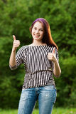 Thumbs up. Young beautiful girl showing two thumbs up, outdoors on natural background royalty free stock photos