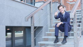 Thumbs Up by Young Businessman Sitting on Stairs Outside Office stock video