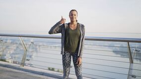 Thumbs up. young girl athlete stands on the balcony, against the background of the metropolis. The girl kindly looks at