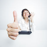 Thumbs up! Young woman happily says OK. Thumbs up shown by a happy, smiling young woman working at her office desk while phoning Royalty Free Stock Photos