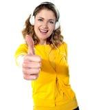 Thumbs-upkvinna som tycker om musik Royaltyfria Bilder