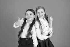 Thumbs ups for the new style. Stylish girls in pigtails dressed for school. Little girls wearing school uniform. School. Children with a fashion forward look stock image