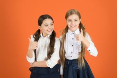 Thumbs ups for school chic. School children with fashion. Little girls wearing trendy uniform. Stylish girls in pigtails royalty free stock images