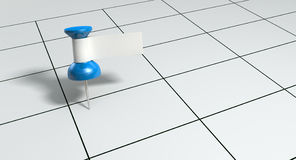 Thumbtack With Blank Label On Generic Calendar. A blue thumbtack with a blank white tape tag attached to it on a generic calendar grid background Royalty Free Stock Image