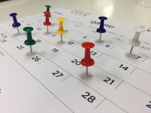 Thumbtack in calendar concept for busy,appointment and meeting reminder. Thumbtack in calendar reminder Stock Image