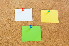Thumbtack pins and notepaper on pinboard. 3 coloured thumbtack pins with notepapers on brown cork pinboard - copy space for your text Stock Images